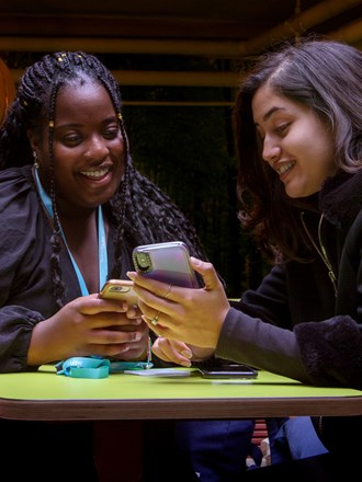 Two students smiling and looking at a phone