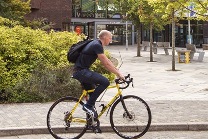 Student cycling outside University of Exeter's campus