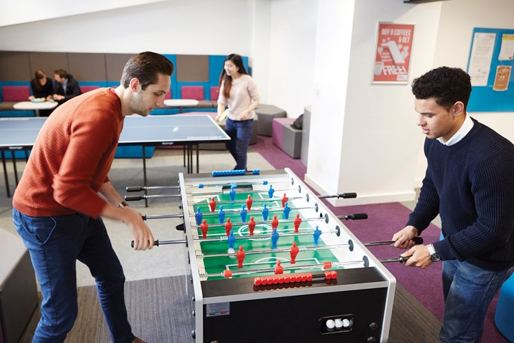 two students playing foosball
