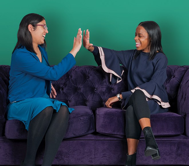 Two women sitting on sofa high-fiving