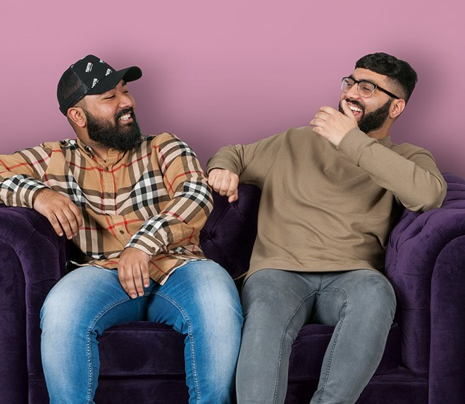 2 men sitting on purple sofa laughing