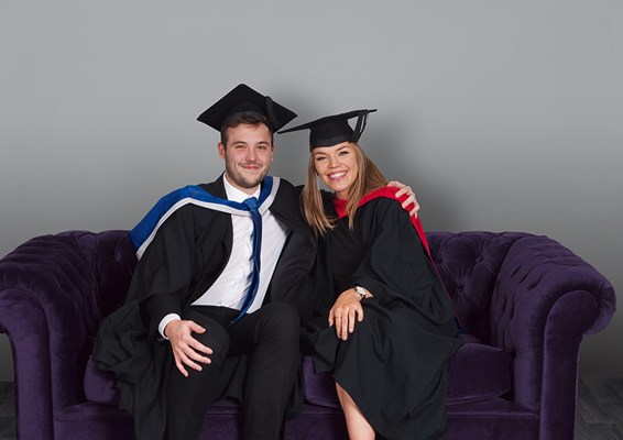 Two University of Law graduates sitting on a sofa
